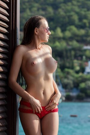Seductive young lady with nude boobies looking away and adjusting knitted panties while standing near building and water on sunny day 写真素材