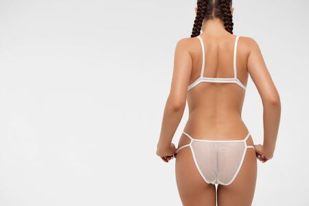 Back view of crop erotic woman with tight braids in white lingerie while holding hands on hips and touching laces of underwear