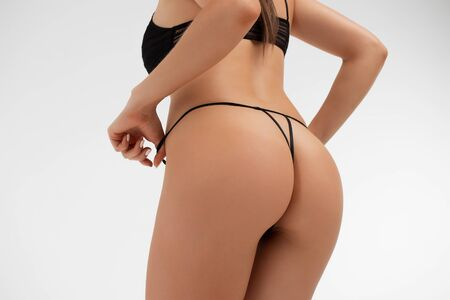 Young lady in lace lingerie leaving buttocks bare