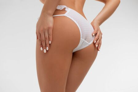 Faceless sexy woman touching panties in studio