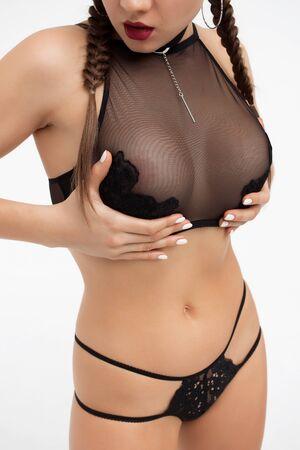 Crop seductive lady touching breast posing in studio