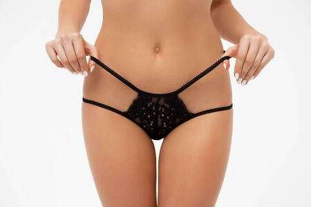 Faceless seductive lady touching lingerie in studio