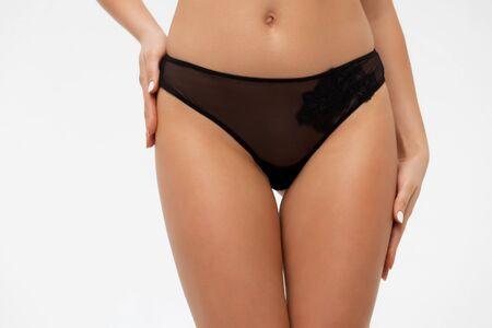 Faceless sexy female in black lingerie posing in studio