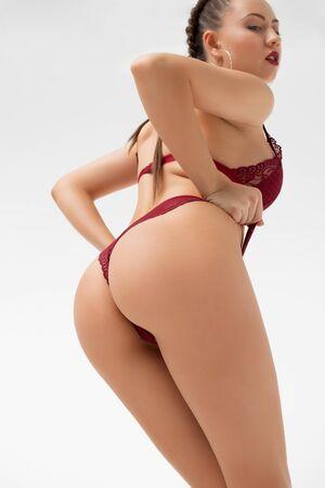 Graceful woman touching lingerie posing in studio Stockfoto