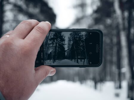 A man takes photos of the winter forest on his phone