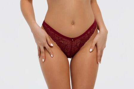 Closeup of crop sexual young woman with hands on lingerie touching panties posing in studio on white background