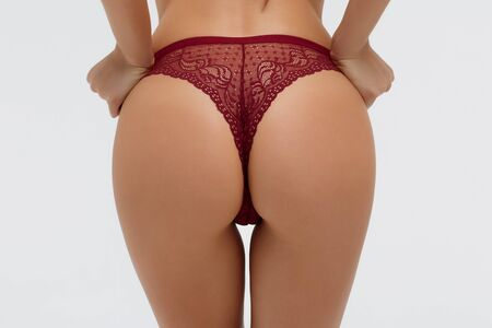 Closeup of faceless gorgeous young woman in red underwear with hands on buttocks posing in studio on white background