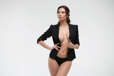 Sexy naked woman in black suit looking at camera