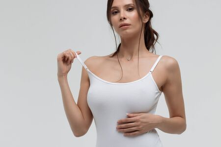 Alluring woman pulling strap of white t shirt and looking at camera