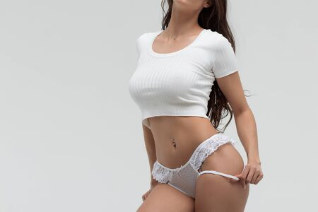 Sensual woman in white t shirt and lace lingerie looking at camera Stock fotó