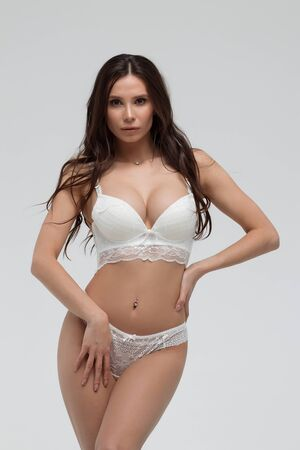 Hot sexy woman in white lace lingerie looking at camera touching body
