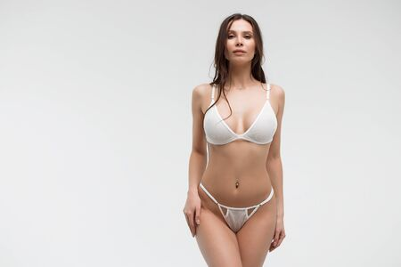 Charming woman with sexy figure in white lingerie looking at camera
