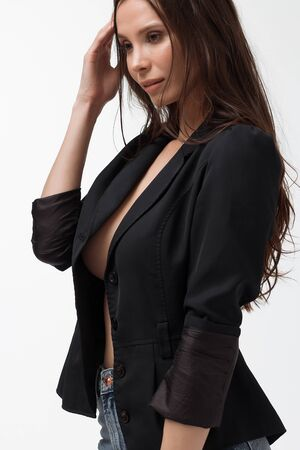 Provocative woman in black suit on naked body looking away Stockfoto