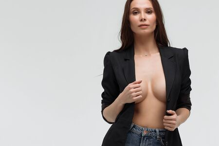 Sexy woman in black suit on naked body looking at camera