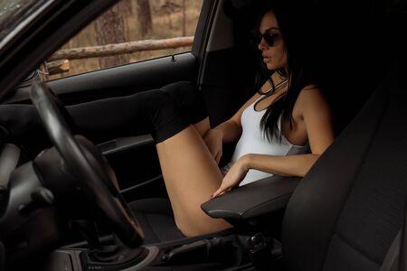 Brunette girl in underwear sitting in the car