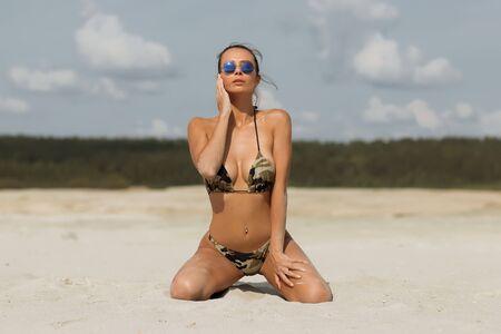 Sensual woman kneeling on beach