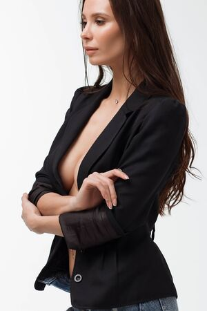 Hot brunette woman with naked breast touching black suit and provocatively looking away in studio Stockfoto