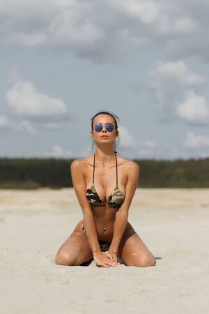 Attractive young female in top and panties closing eyes and touching hair while standing on knees on sandy beach against cloudy sky on resort Stockfoto