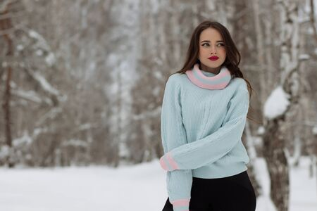 Young woman in trendy warm clothes smiling for camera and adjusting long hair while standing near forest on cold winter day