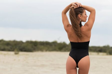 Back view of gorgeous young woman with long hair in trendy swimsuit standing on blurred nature background