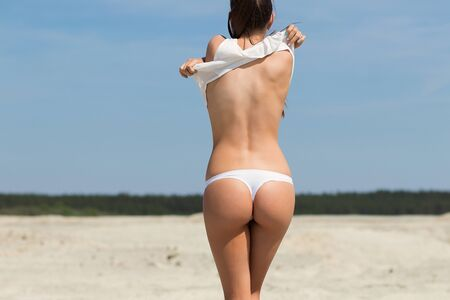 Back view of seductive female in thongs taking off white top while standing on sandy beach against blue sky on sunny day on resort