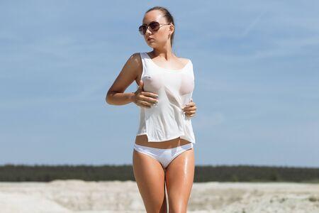 Vue arrière d'une femme séduisante en tongs décollant d'un haut blanc en se tenant debout sur une plage de sable contre le ciel bleu par une journée ensoleillée sur le complexe