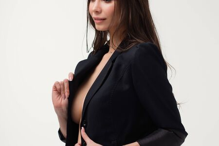 Provocative woman in black suit on naked body looking away Reklamní fotografie