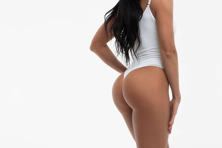 Back view of faceless seductive young woman touching white swimsuit showing sexual buttocks posing in studio on white background