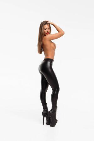 Attraente donna affascinante in pantaloni di pelle e tacchi alti