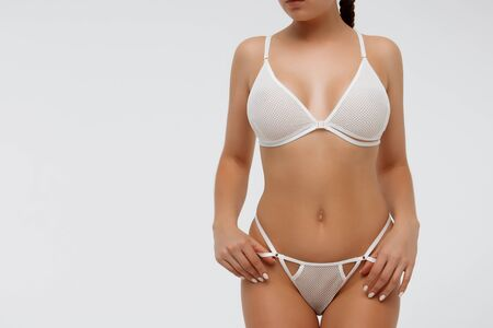 Cropped young lady with tight braids wearing white lingerie holding laces of thongs and looking away