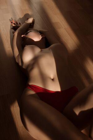 Topless graceful female lying on floor 版權商用圖片