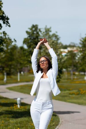 Confident sensual woman in stylish white suit standing with eyes closed and arms raised and enjoying life and freedom on street against blurred walkway and green trees growing on flowered lawns