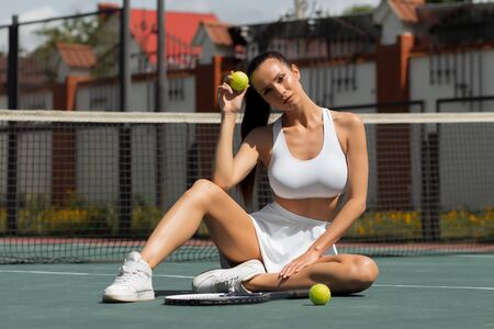 Seductive slim female in sportswear and visor looking away and dreaming while sitting alone on court beside racket and touching ball in sunny day