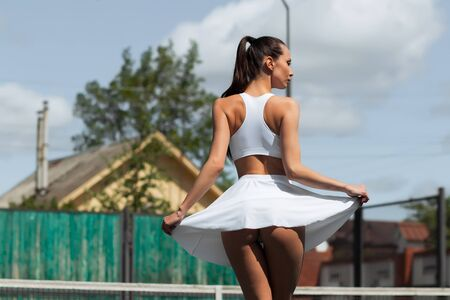 Back view of sensual woman lifting white skirt and showing perfect buttocks while spinning around on tennis court in suburb