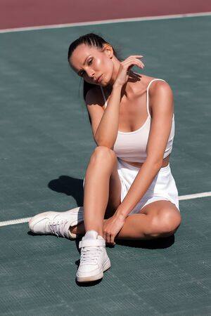 Tennis player sitting on court and resting