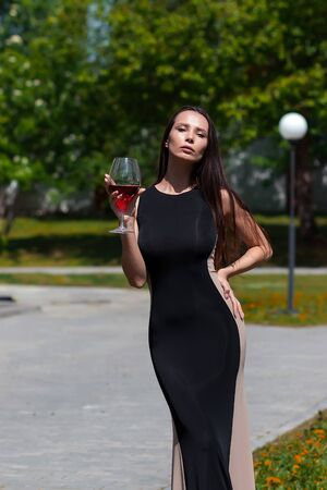 Elegant woman with wine in park