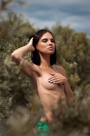 Naked woman standing in bushes Stock Photo
