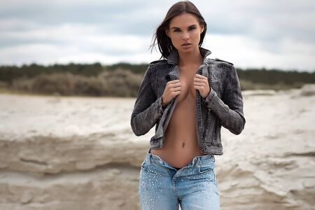 Seductive woman in denim outfit in nature