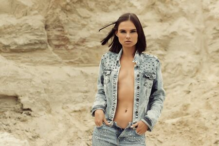 Attractive female model in jeans looking at camera and covering breast with denim jacket on blurred background of countryside