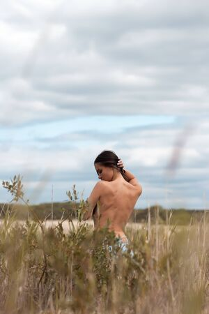 Naked woman standing in bushes Archivio Fotografico