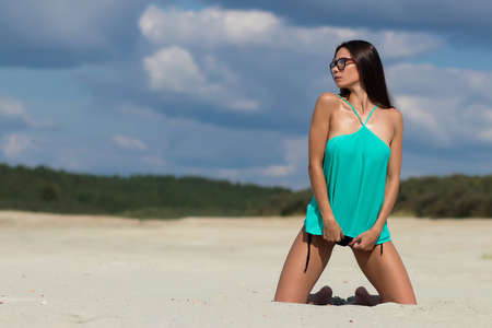 Sensual woman kneeling on beach Banque d'images - 150962818