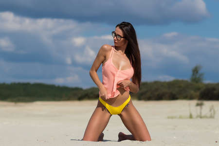 Sensual woman kneeling on beach Banque d'images - 150962888