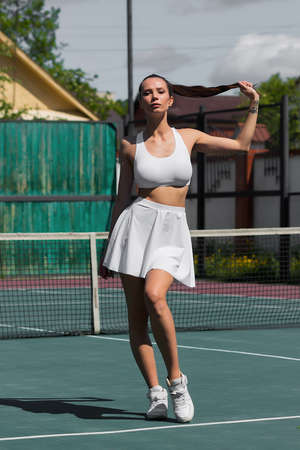 Back view of sensual woman lifting white skirt and showing perfect while spinning around on tennis court in suburb