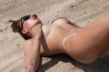 Sensual topless woman lying on sandy beach