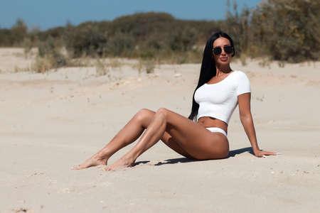 Sensual slim woman sitting on sandy beach