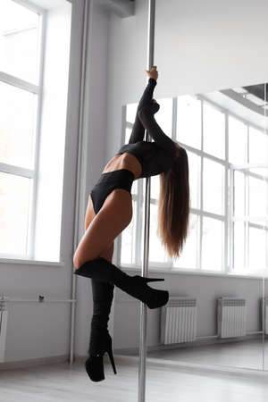 Slim woman dancing on pole