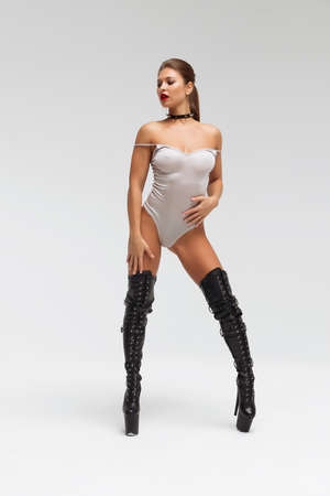 Sexy young woman in bodysuit and boots