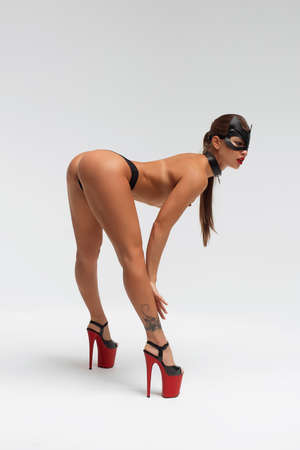 Seductive tanned woman in mask and high heels