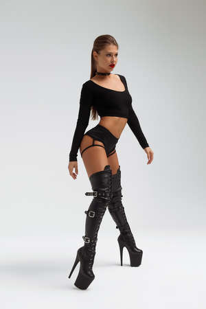 Alluring young woman in black underwear and boots 免版税图像