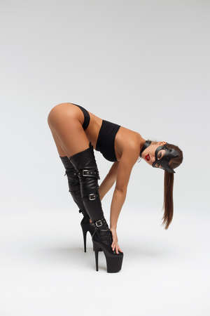 Sexy woman in mask and high leather boots
